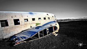 Flugzeugwrack mit Bergmassiv im Hintergrund